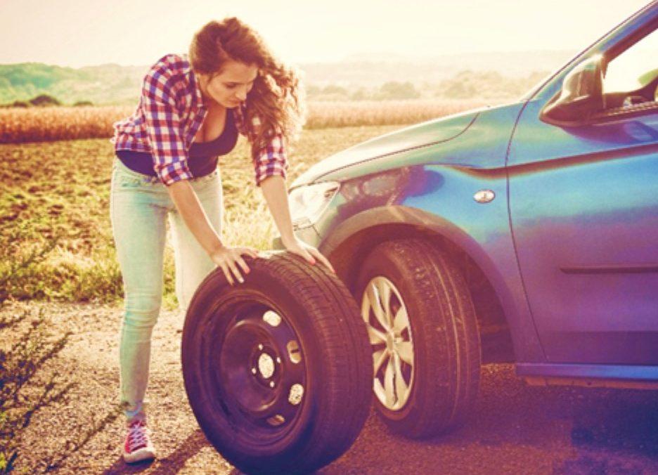Frau beim Reifenwechsel unter 3